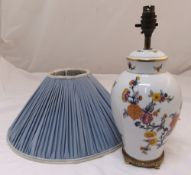 A porcelain baluster table lamp decorated with flowers and leaves mounted on a gilded metal base