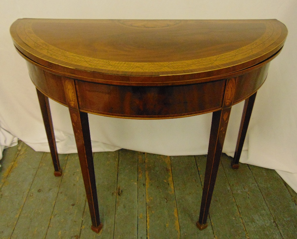 A Regency mahogany and satinwood inlaid demilune card table on four tapering rectangular legs, 74