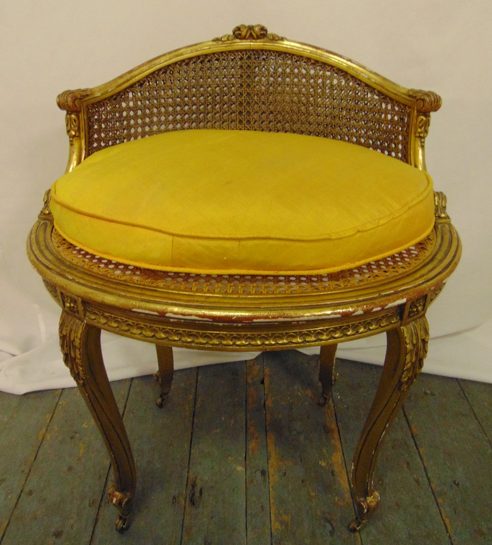 A gilded wooden and bergere French boudoir chair of oval section on four cabriole legs, 67 x 54 x