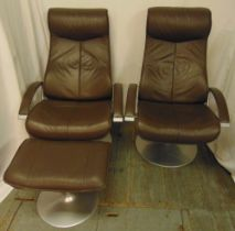 A pair of reclining leather swivel chairs and one matching foot stool