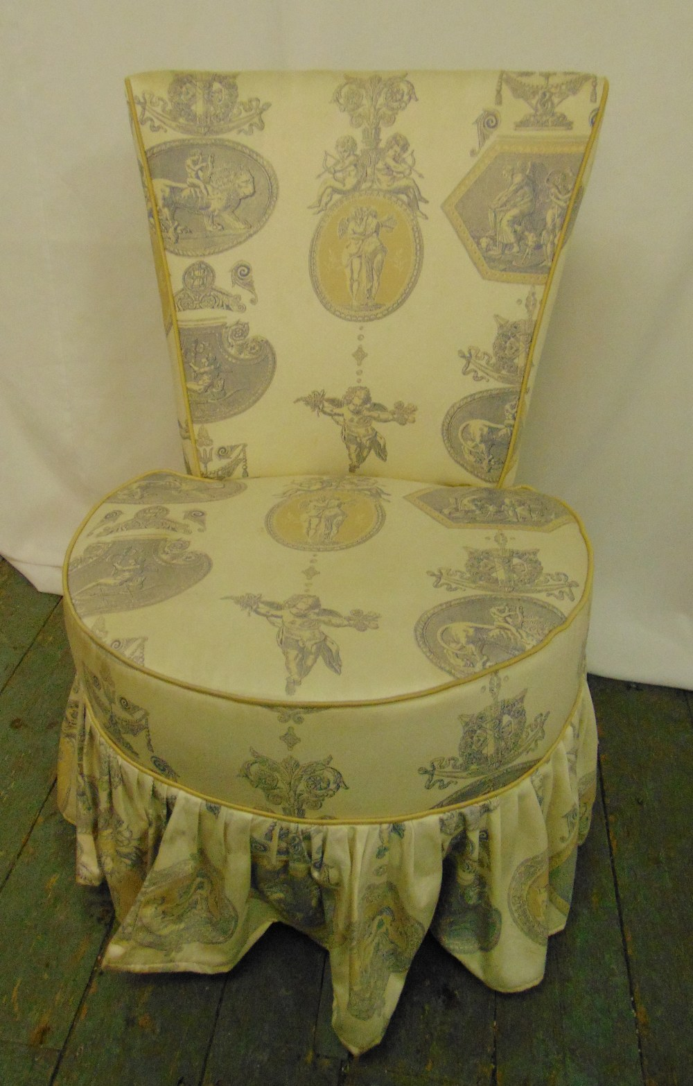 An upholstered boudoir chair of circular form with tapering rectangular back, 76 x 51 x 52cm