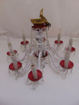 A continental white overlaid red glass chandelier with eight scrolling branches supporting candle