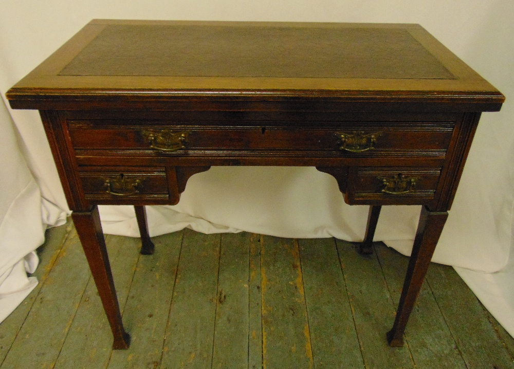 A mahogany rectangular kneehole desk, the three drawers with brass handles on four tapering