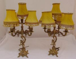 A pair of gilt metal table lamps, the scrolling arms supported by putti on raised bases with four