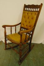 An oak rocking chair of customary form with upholstered seat and back, 109 x 56cm