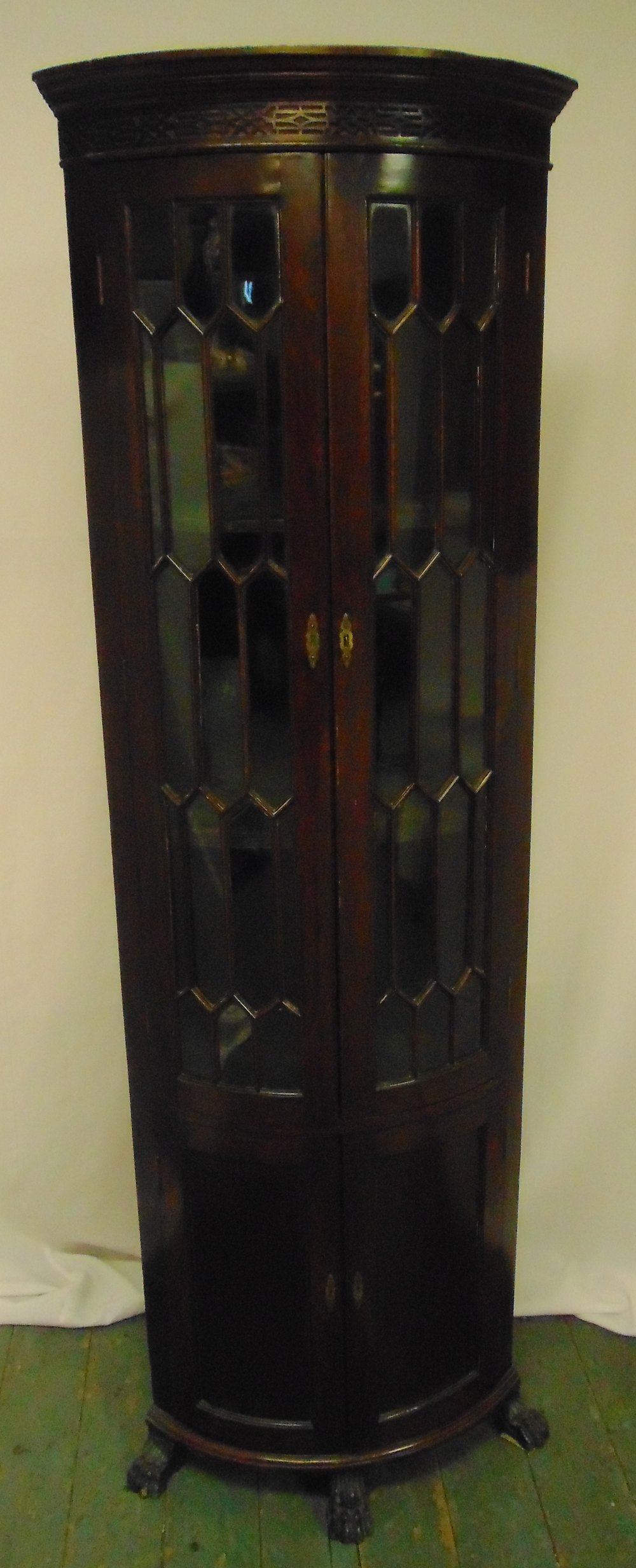 A mahogany glazed corner cabinet, demilune on four supports, 186 x 59.5cm