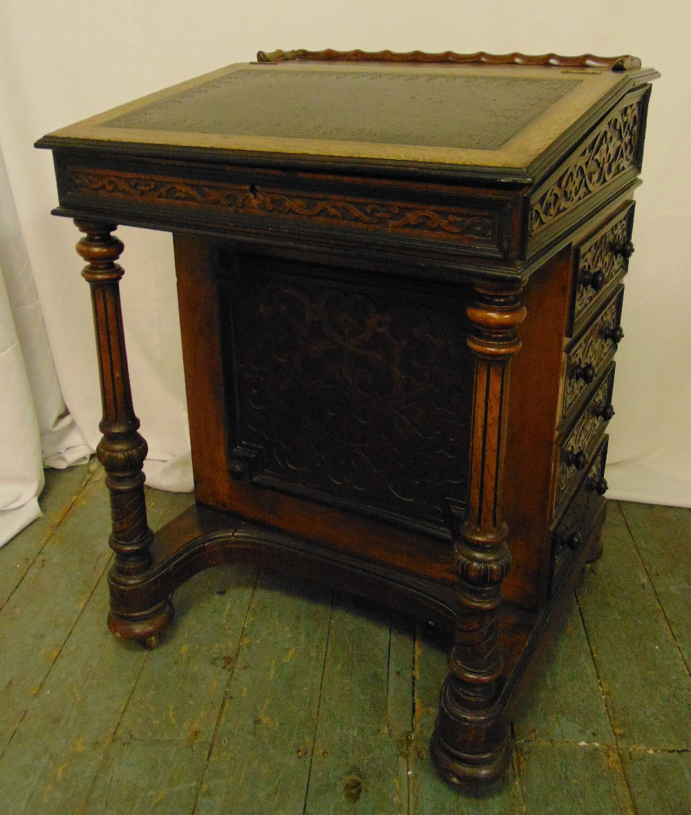 A Victorian oak Davenport of customary form with hinged leather inset top and four side drawers with
