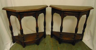 A pair of oak side tables, the angled tops with baluster supports on four rectangular legs, 72 x
