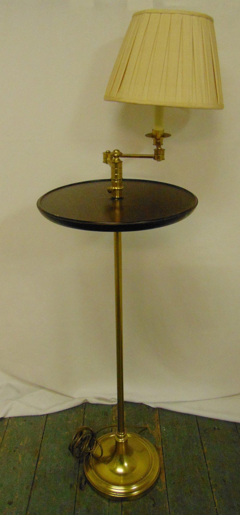 A brass and mahogany side table, circular on tubular stem with raised circular base and adjustable