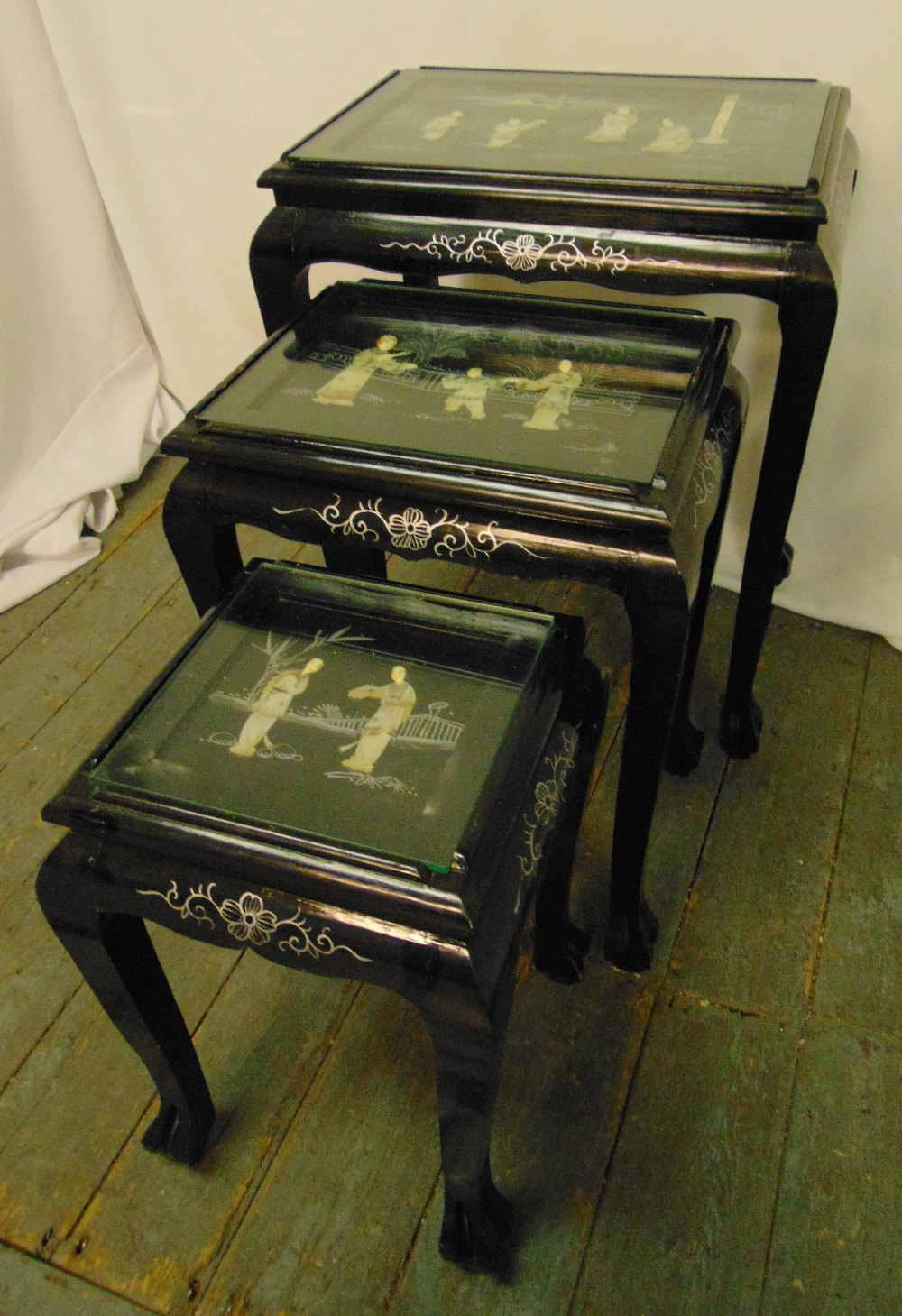 A nest of three oriental tables, the tops with applied mother of pearl figurines within a stylised