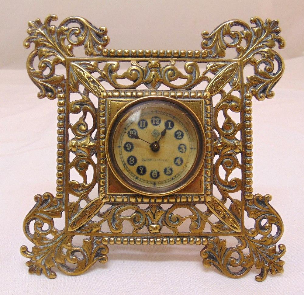A brass easel clock, scroll pierced frame, the circular dial with Arabic numerals, 17.5 x 17.5cm