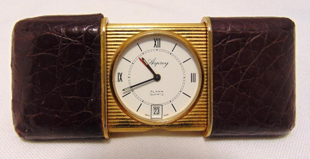 An Aspreys miniature self winding travel clock with crocodile leather case