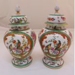 A pair of porcelain oriental style baluster vases with pull off covers decorated with birds, flowers