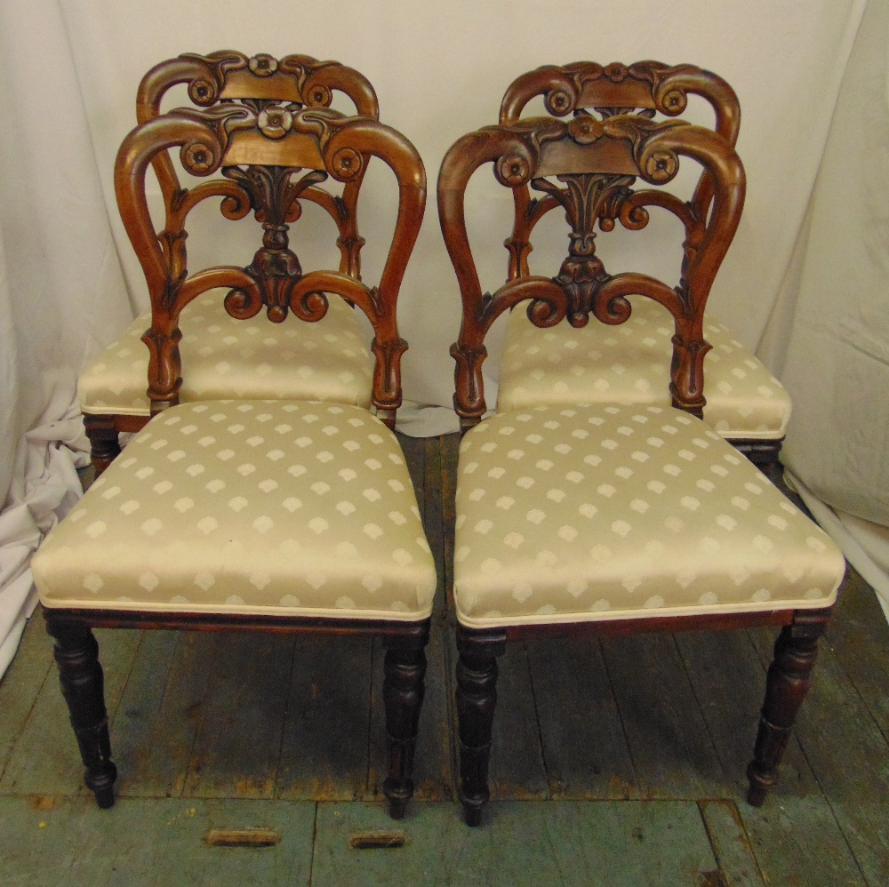 A set of four Victorian mahogany dining chairs with scroll pierced backs on turned tubular legs