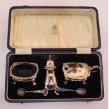 A hallmarked silver cased condiment set to include salt, pepper, mustard and two condiment spoons