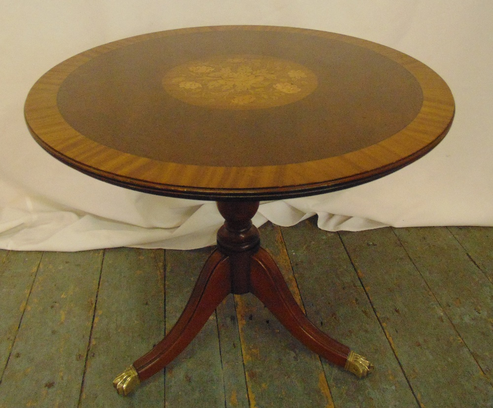 A circular mahogany side table with inlaid satinwood to the centre all on three outswept legs with