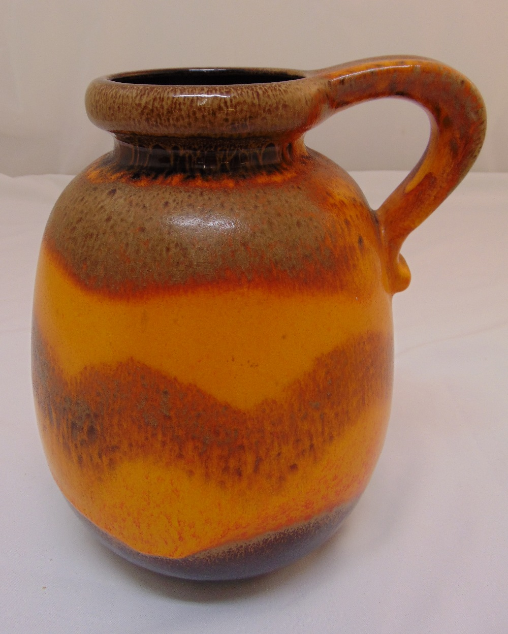 A mid 20th century continental polychromatic ceramic jug with scroll handle, 30cm (h)
