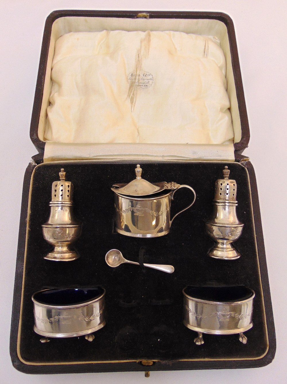 A cased set of silver condiments to include a pair of pepperettes, a pair of salts, a mustard pot