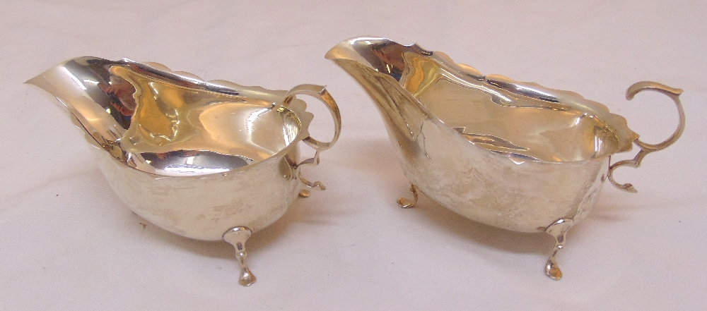 A pair of hallmarked silver sauce boats oval with scalloped rims, scroll handles on three pad