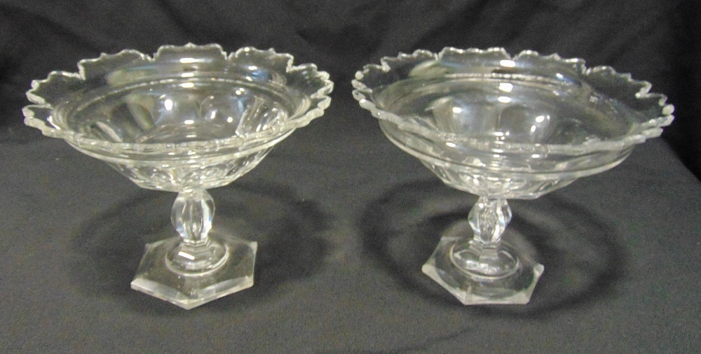 A pair of Irish Regency glass comports of circular form with scroll borders, knopped stems on raised
