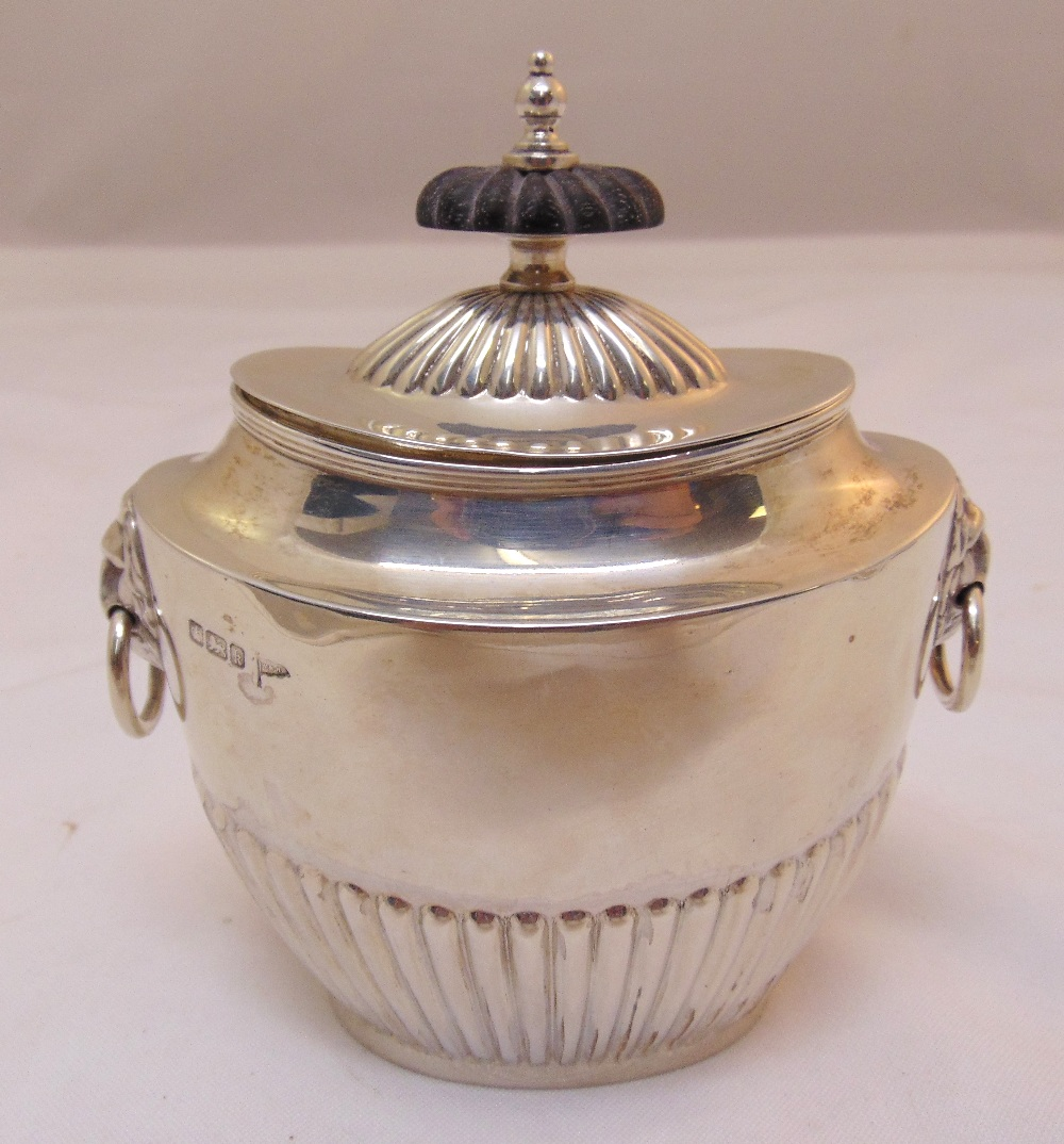 A hallmarked silver shaped oval tea caddy part fluted with lion mask ring handles pull off cover