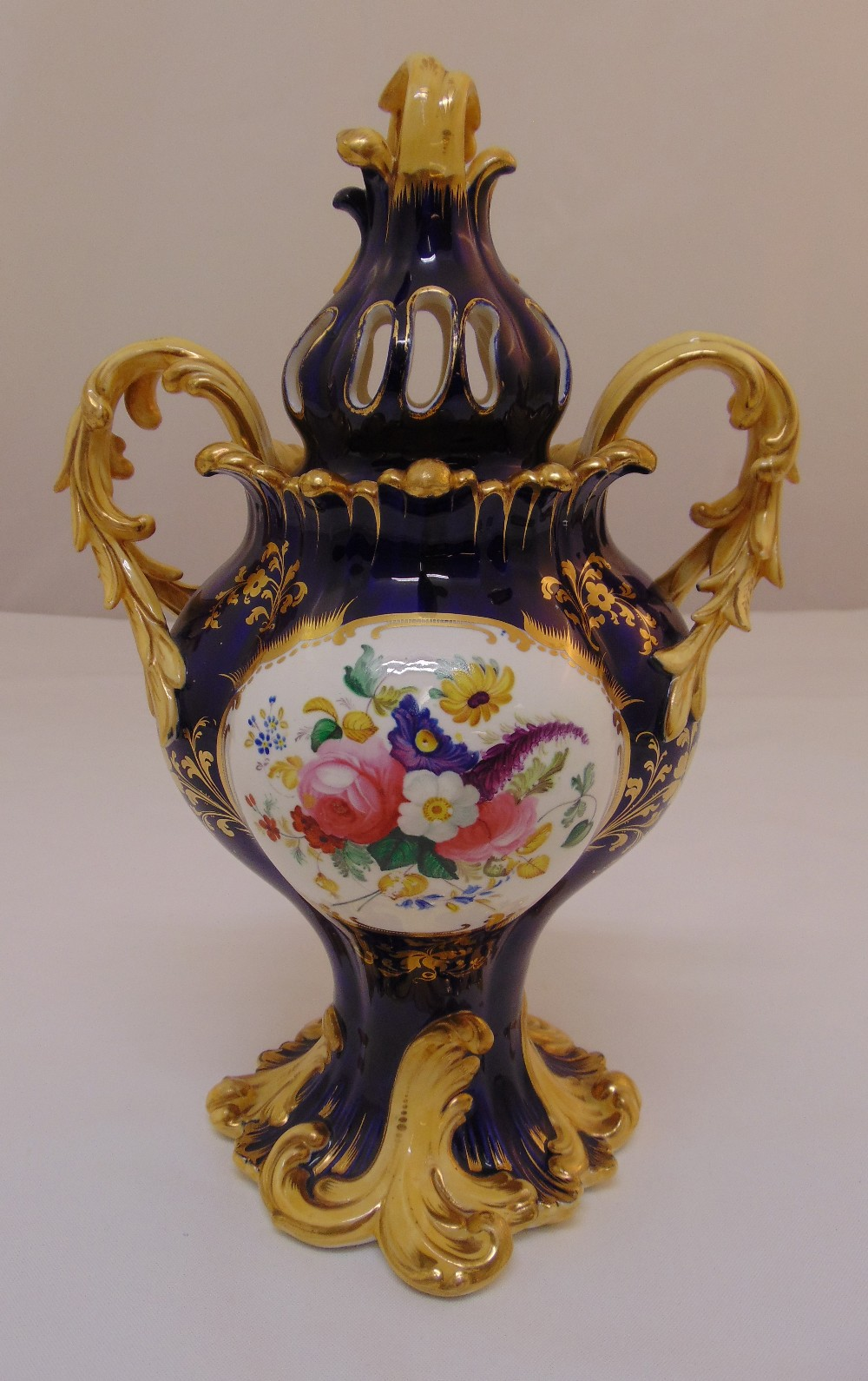 A 19th century Coalport pot pourri vase and cover decorated with panels of floral sprays, a romantic