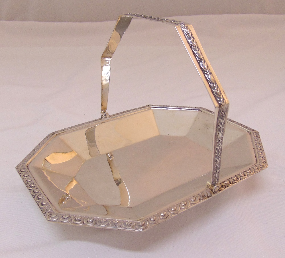 A hallmarked silver octagonal fruit stand with swing handle on four scroll feet, London 1923, approx
