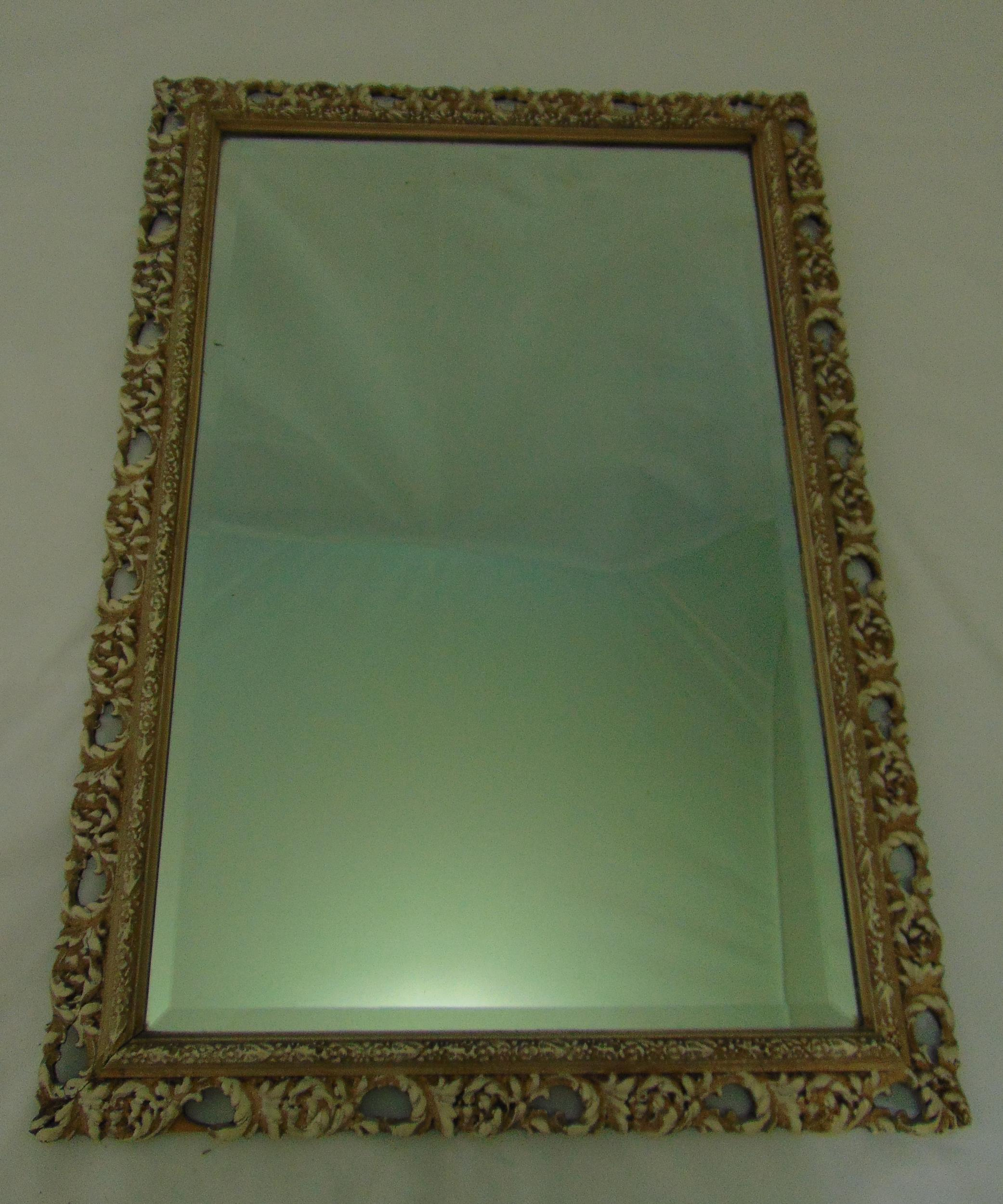 A rectangular scroll pierced and stained wooden mirror with bevelled edge, 73.5 x 51cm