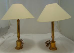 A pair of brass table lamps of cylindrical form on raised cylindrical bases, to include shades, 62cm