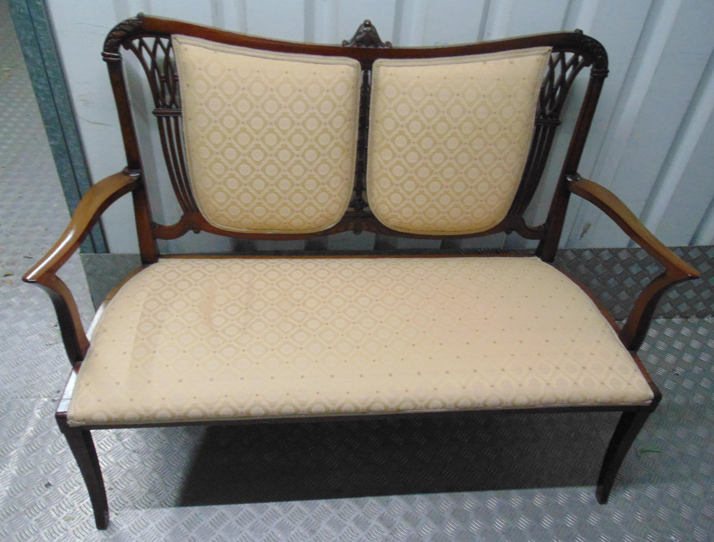 An Edwardian mahogany upholstered settle with scrolling arms and pierced back on four cabriole legs