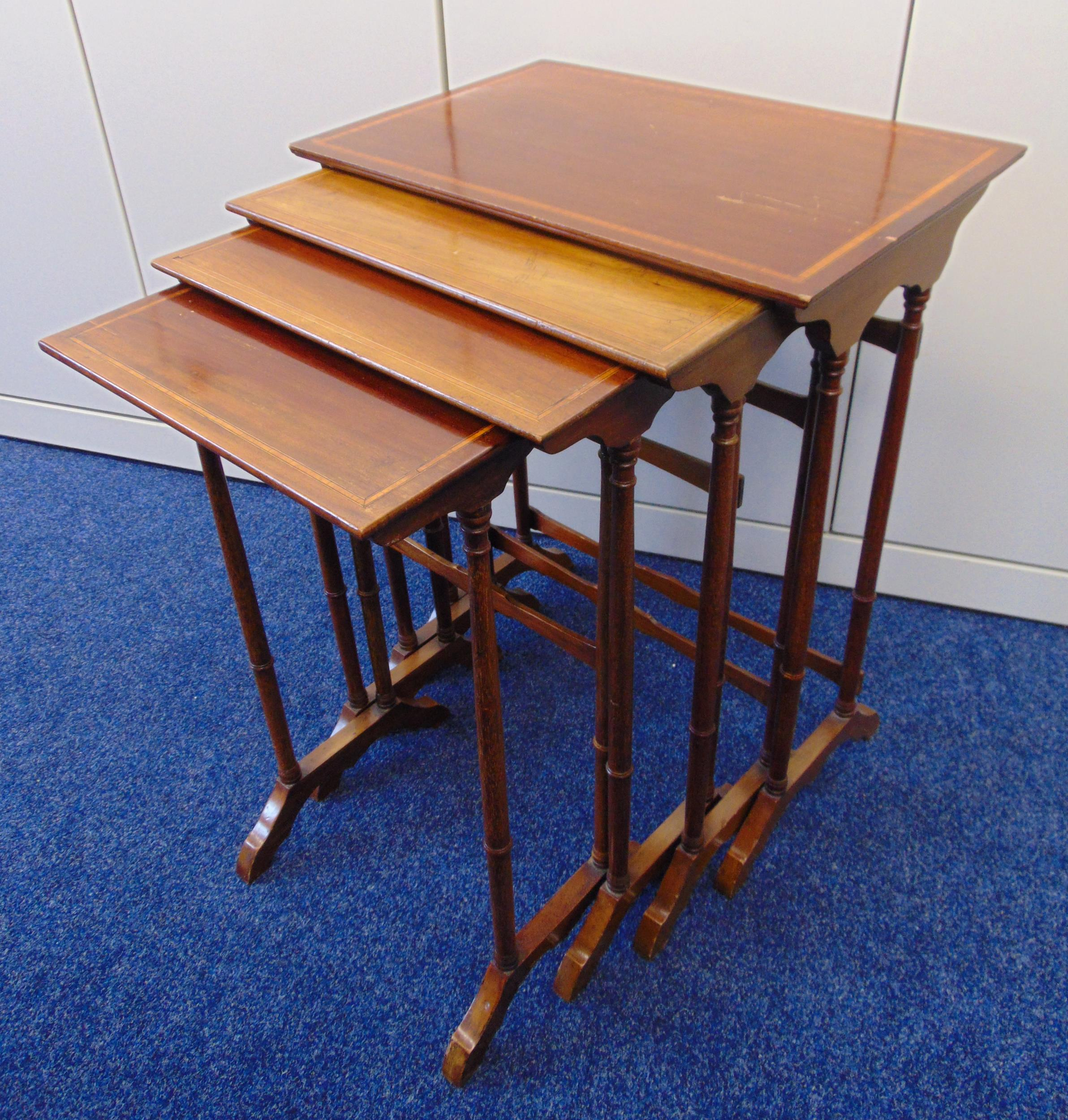 A nest of four rectangular tables inset with satinwood banding on scroll supports, 68.5 x 35.5 x
