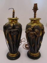 A pair of Art Nouveau style table lamps, copper and brass ovoid form with applied flowers and leaves