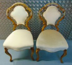 A pair of continental upholstered occasional chairs on scroll legs