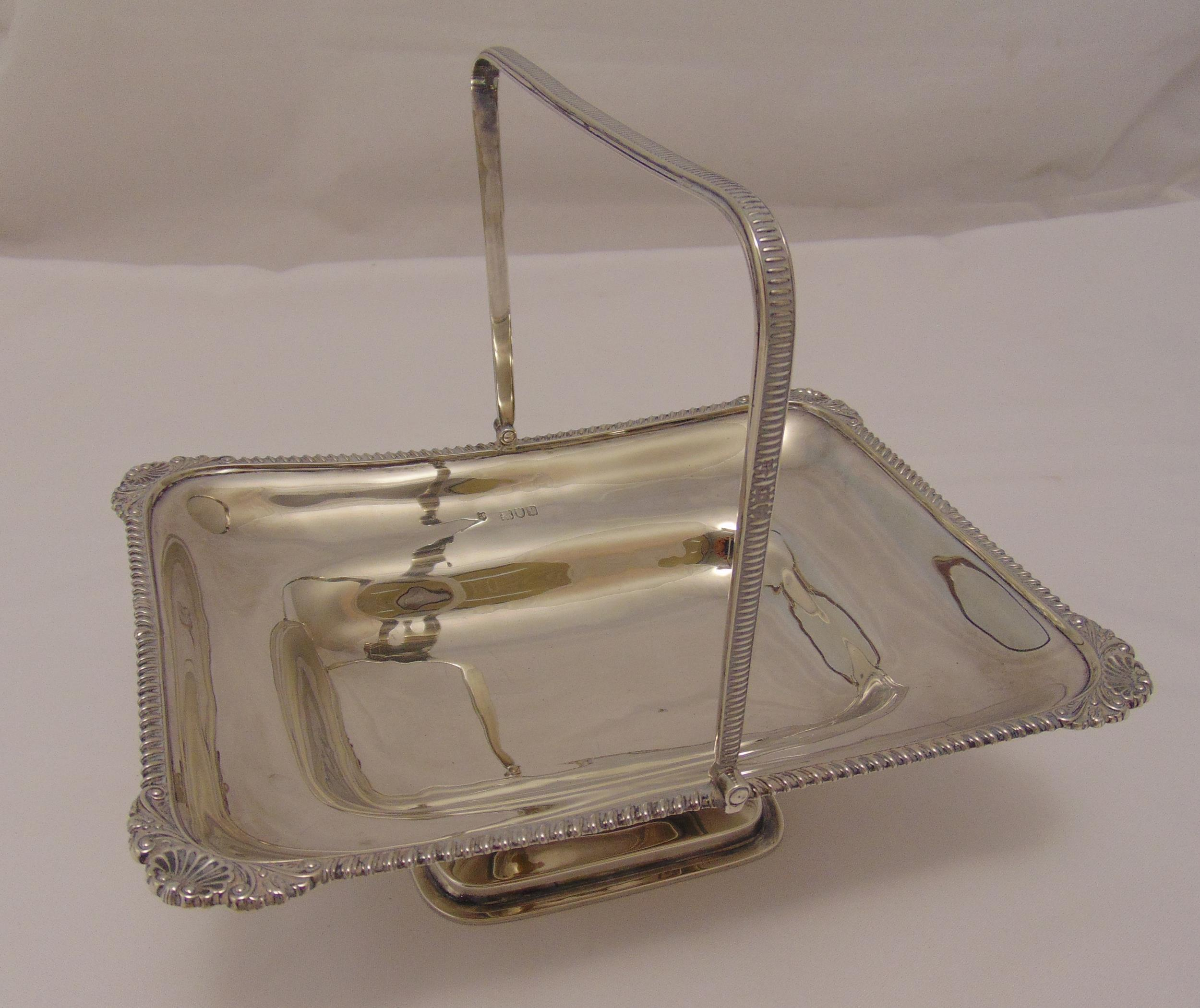 A hallmarked silver fruit basket rounded rectangular, gadroon and shell border with swing handle