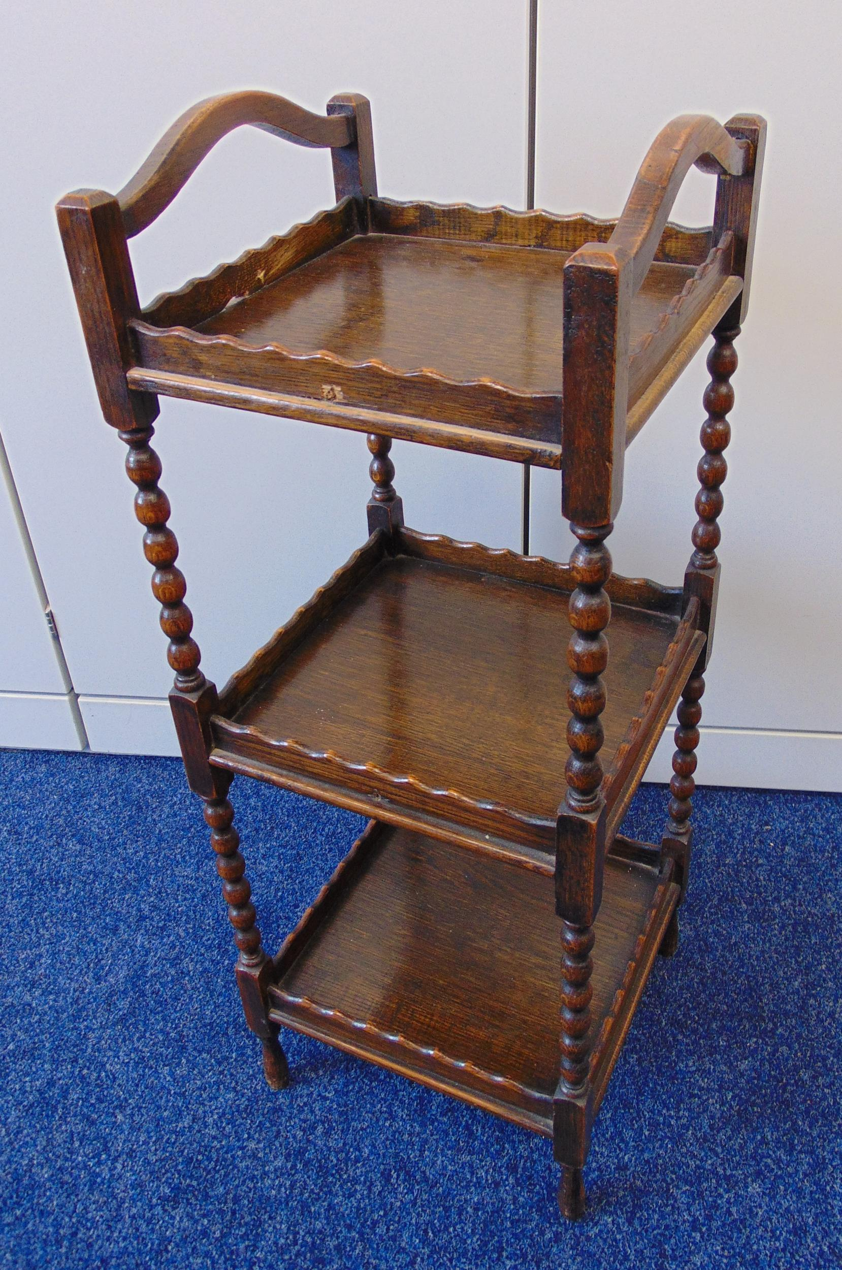 An oak three tier whatnot, square form with two side handles on four tapering cylindrical legs, 76 x