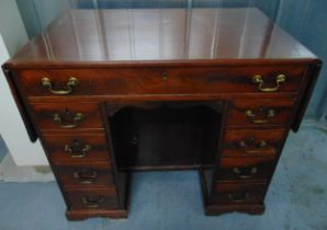 A rectangular mahogany kneehole desk with drop flap to the sides, nine drawers with brass swing