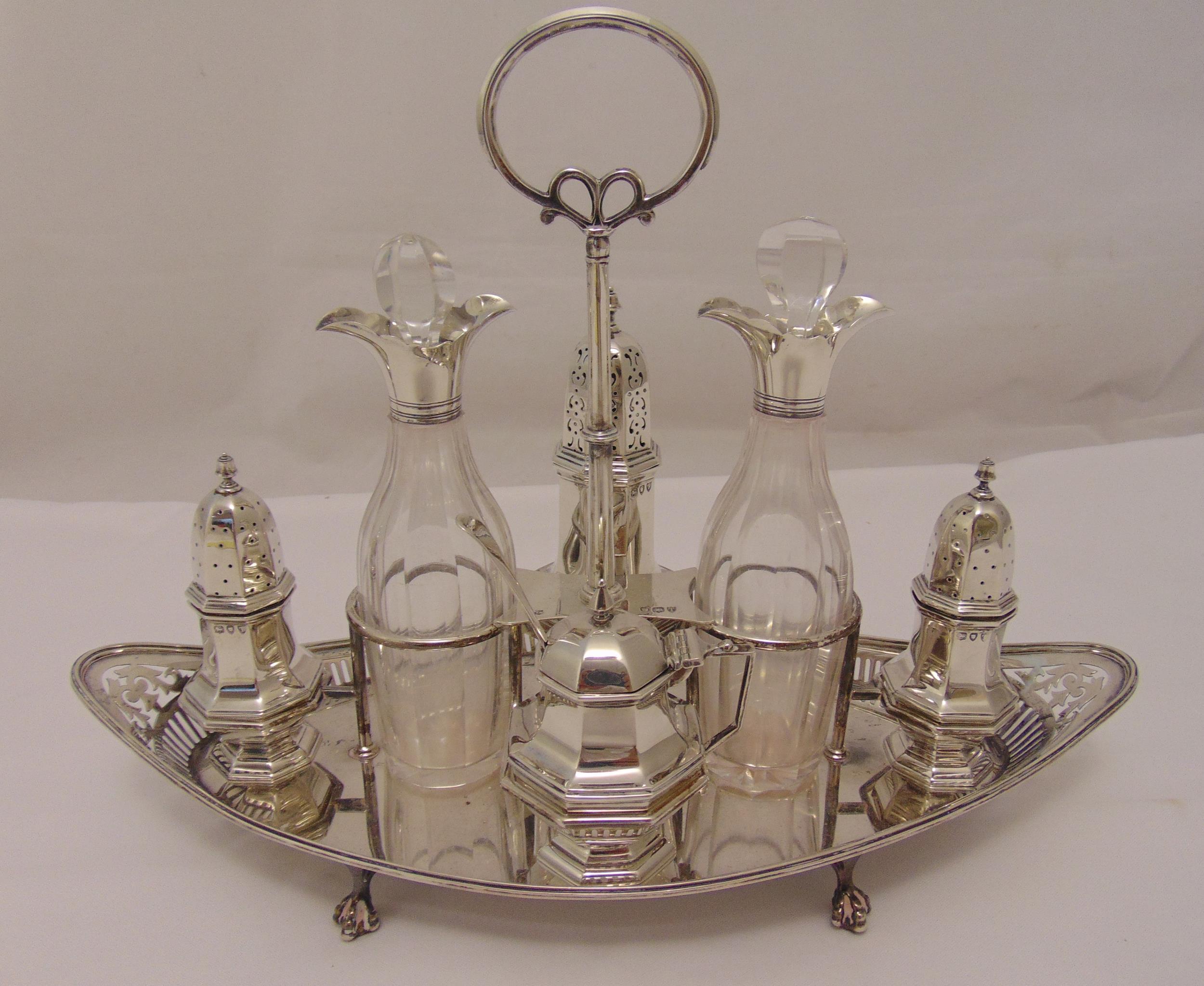 A Victorian hallmarked silver cruet set comprising a sugar sifter, a mustard pot with spoon, a