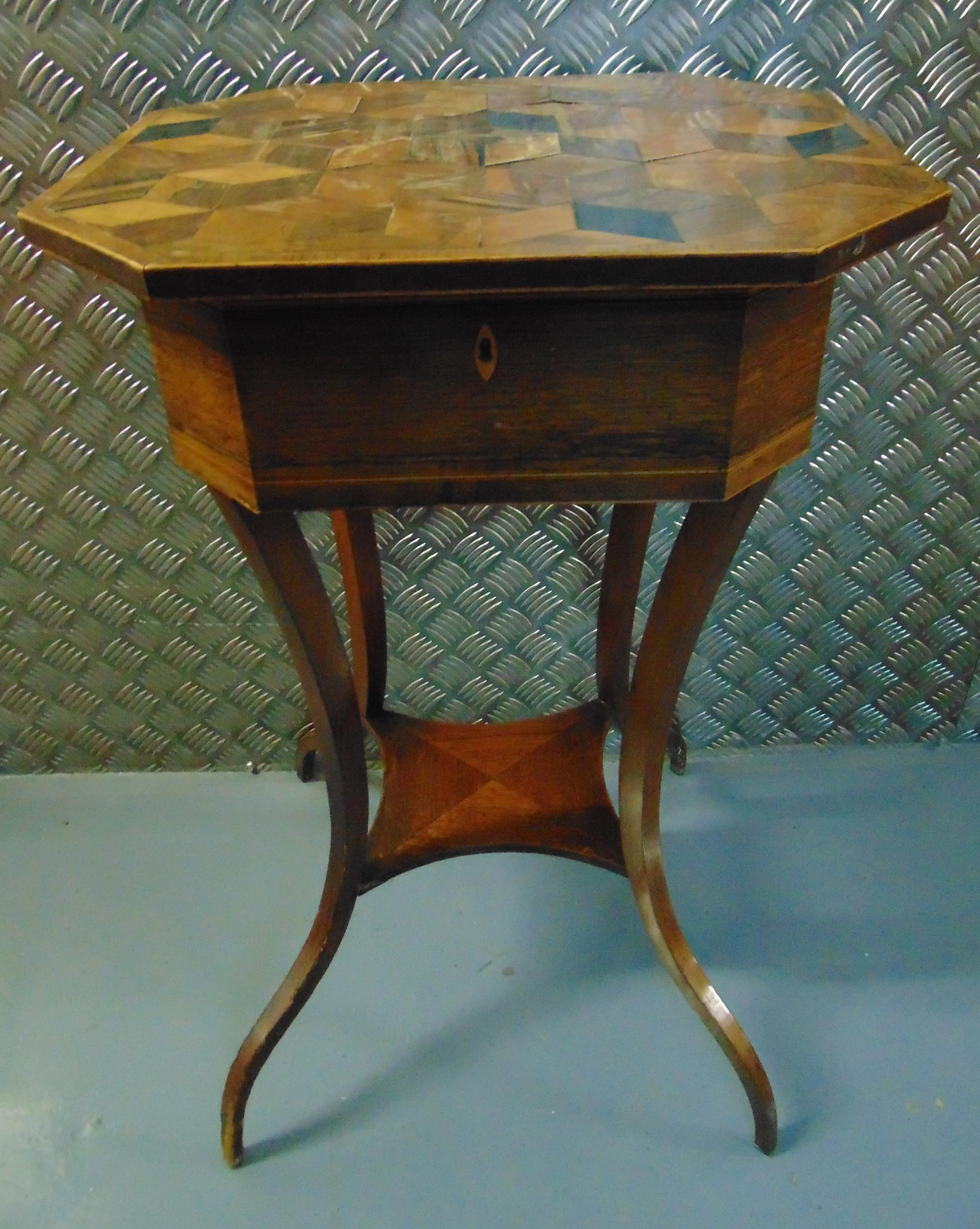 A mahogany inlaid needlework table of elongated octagonal form the hinged cover revealing a lined