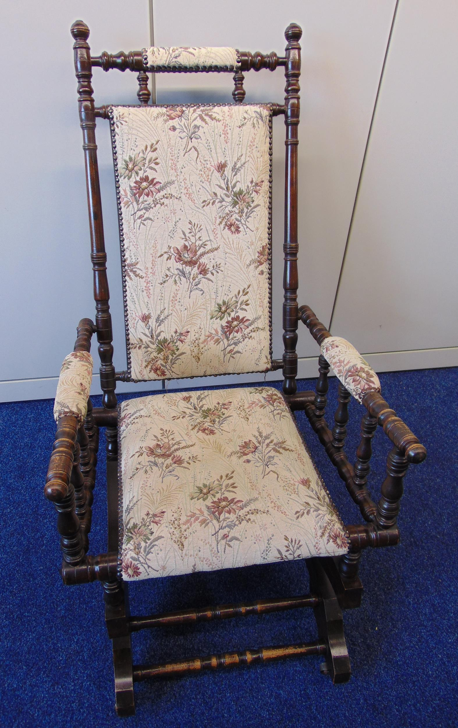 An oak rocking chair with upholstered seat and back and turned sides, arms and back