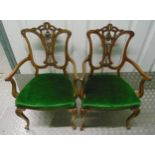 A pair of Edwardian occasional armchairs with scrolling arms and scroll pierced backs on four leaf