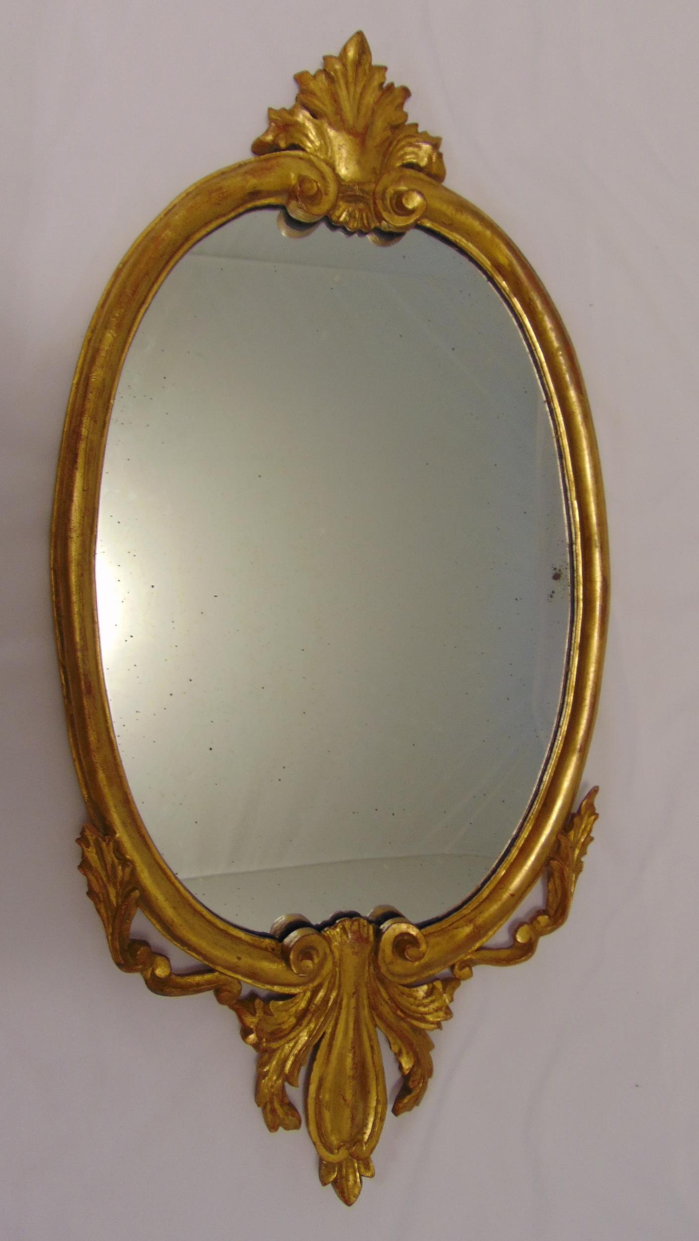 A gilded wooden oval wall mirror, 76 x 38cm