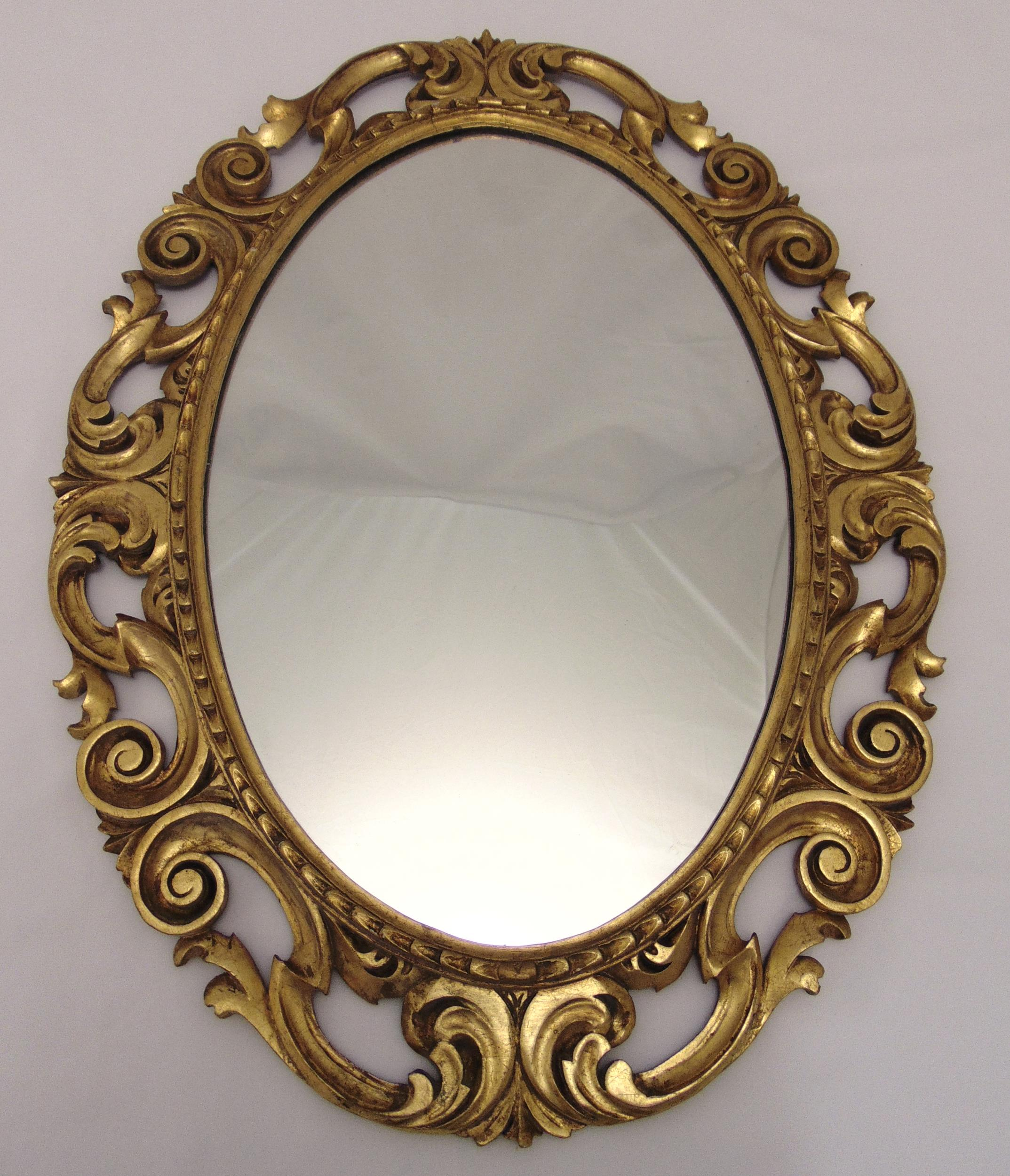 An oval gilded wooden wall mirror, pierced and carved with scrolls and stylised leaves, 77 x 57.5cm