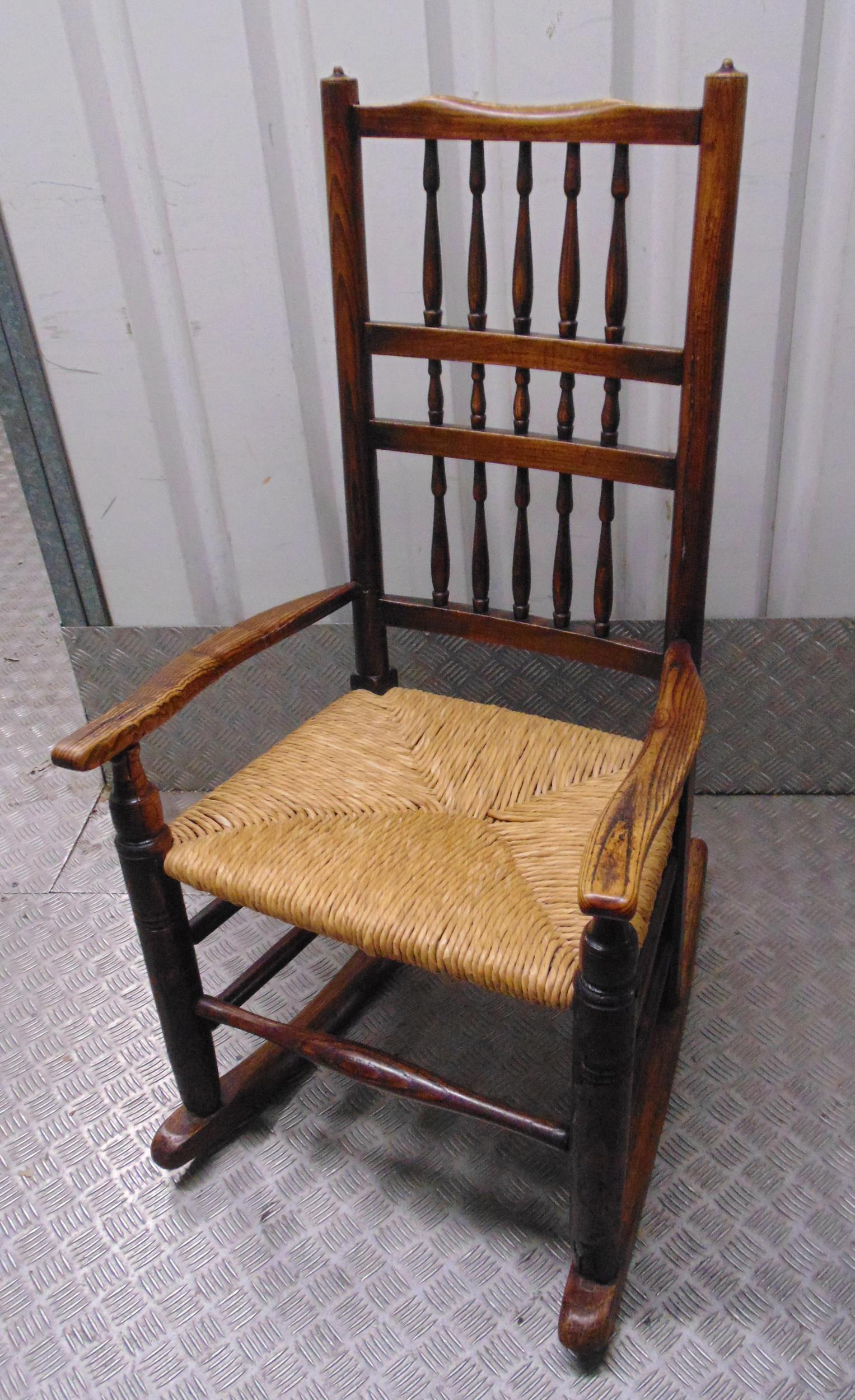 A Victorian oak Cotton Mill spindle rocking chair with rush matting seat