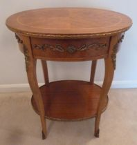 An oval mahogany and Kingswood side table with applied gilded mounts and a single drawer on four