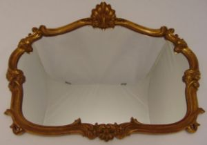 A shaped oval gilded wooden wall mirror carved with scrolls and shells, 70 x 81cm