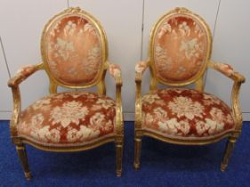 A pair of 19th century continental upholstered salon chairs, the legs, arms and backs carved with