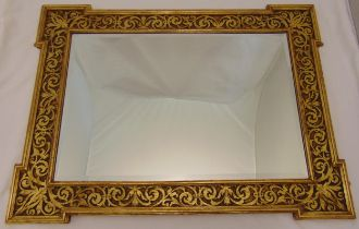 A shaped rectangular bevelled edge wall mirror mounted in a carved low relief gilded wooden frame,