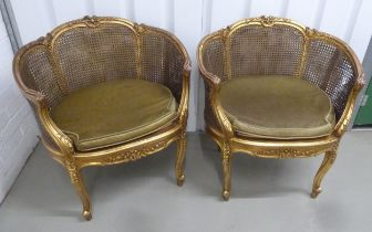 A pair of French style gilded wood and bergere armchairs with removable upholstered seats on four