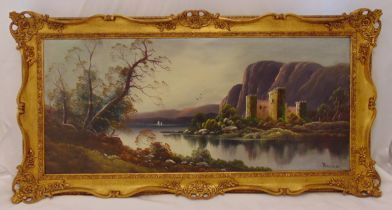 A framed oil on canvas landscape with a lake and a castle in the background, indistinctly signed