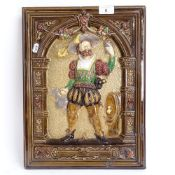 A large 19th century polychrome glazed plaster relief wall plaque, depicting a man in Tudor clothing